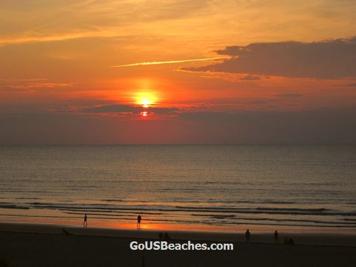Colorful Cocoa Beach Florida Sunrise over Atlantic Ocean with red clouds and reflection on beach