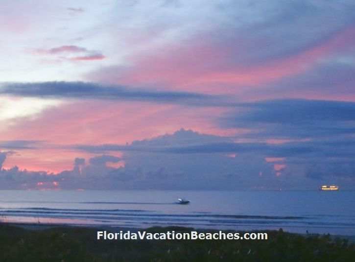 Colorful Cocoa Beach Florida Sunrise over Atlantic Ocean with clouds and Lights of a Cruise Ship + a small boat going by