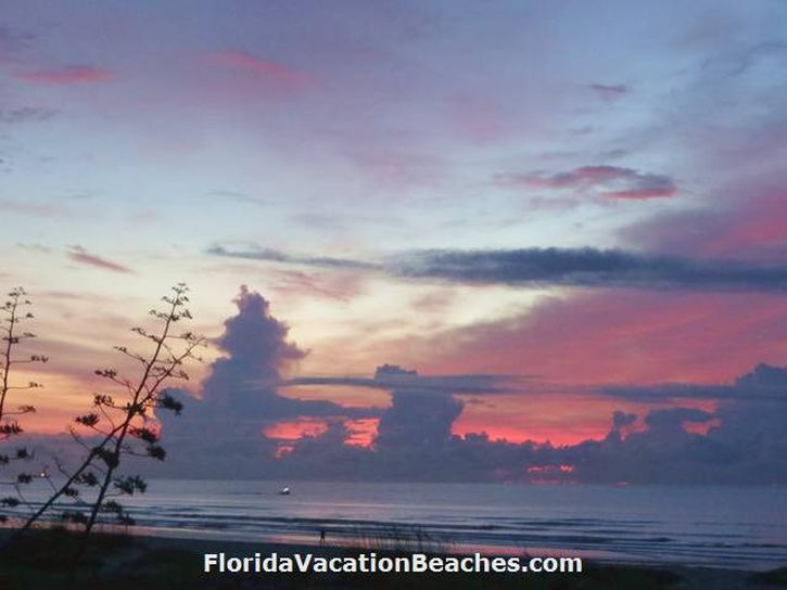 Colorful Cocoa Beach Florida Ocean Sunrise over Atlantic Ocean with clouds and a small boat going by